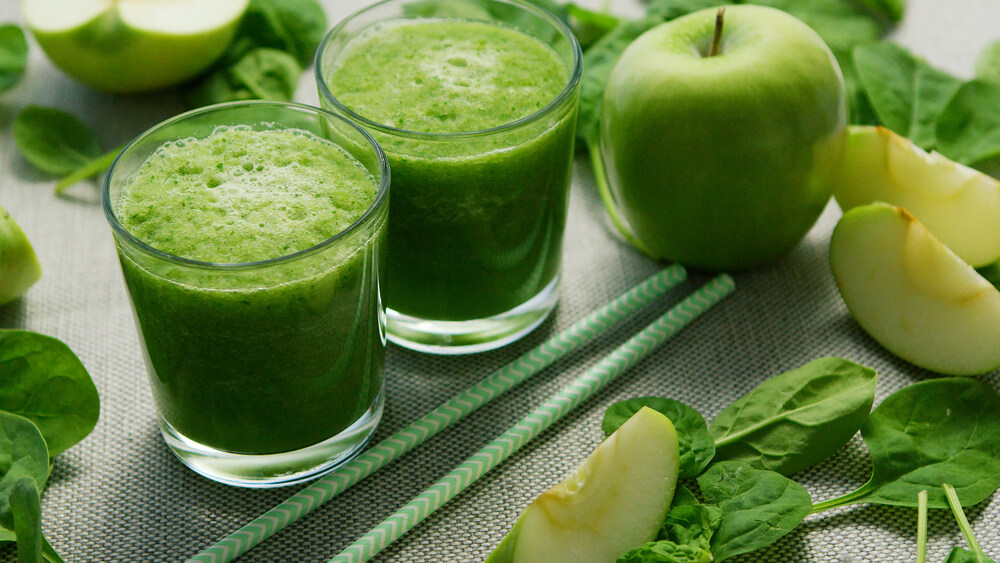 Two glasses of green juice, with apples and spinach