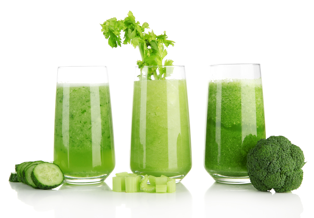 Three glasses of green juice against white, with pieces of cucumber, celery and broccoli