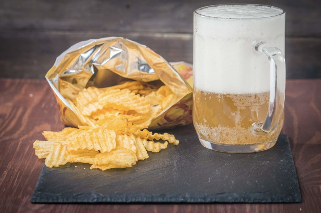 Beer glass with foam and bag of chips