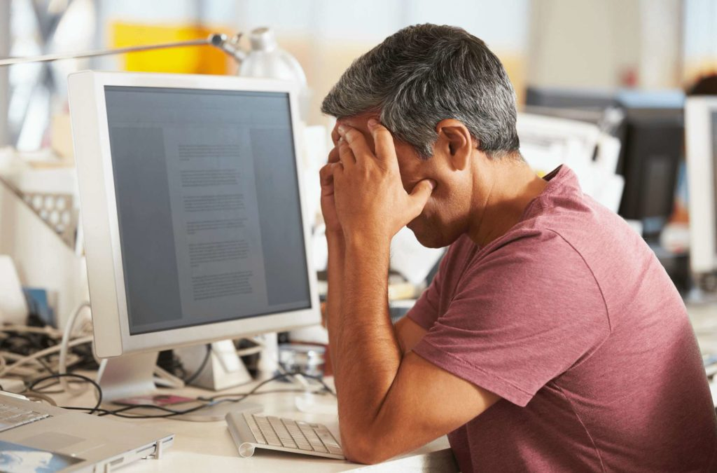 Stressed man sitting at his desk with hands covering face