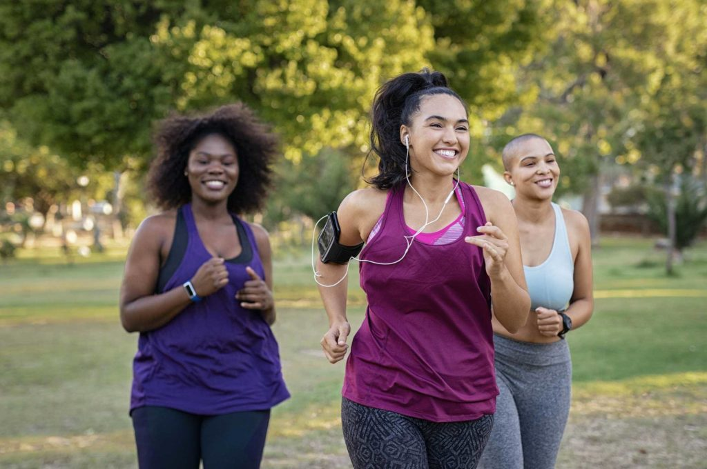 Three smiling women jogging in a park