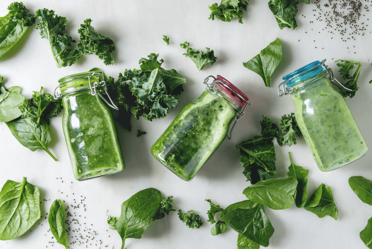 bottles of green juice and kale and spinach